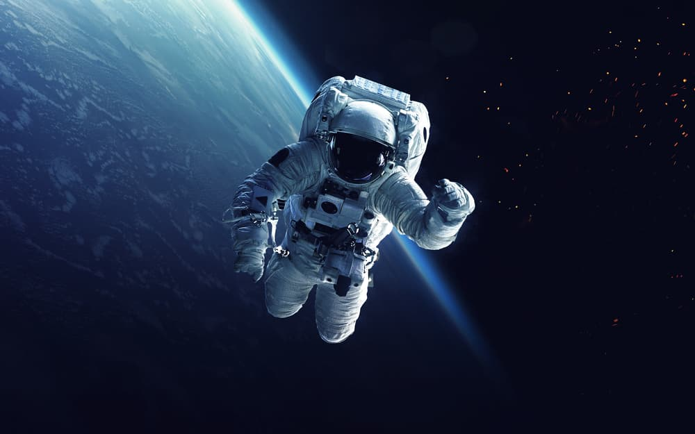 Astronaut waving in space with earth in the background