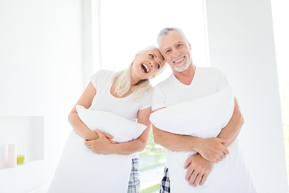 Happy older couple holding pillows