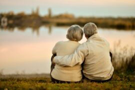 Older Couple sitting by a lake at sunset