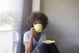 Woman sipping from mug and saucer